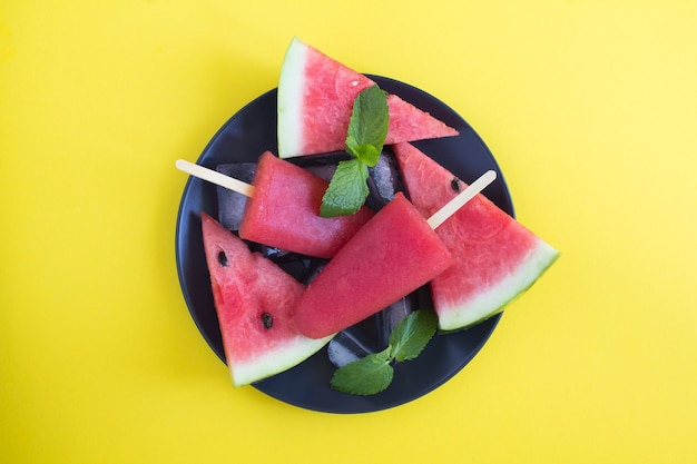 Top view of popsicles with watermelon on the black plate on the yellow background. close-up.