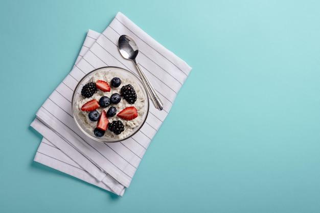 복사 공간 파란색 배경에 옷감 냅킨에 딸기, 블루 베리, 블랙 베리와 유리 그릇에 상위 뷰 죽. 건강한 아침 식사 개념