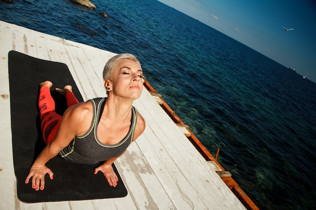 Top view portrait of adult blond woman with short haircut practices yoga on the pier against the background of the sea and blue sky