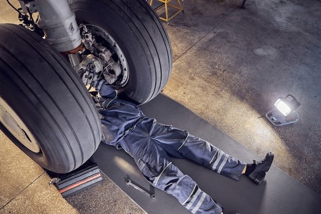 Top view portrait of aircraft engineer doing some maintenance on a landing gear of a big aircraft in a service hangar