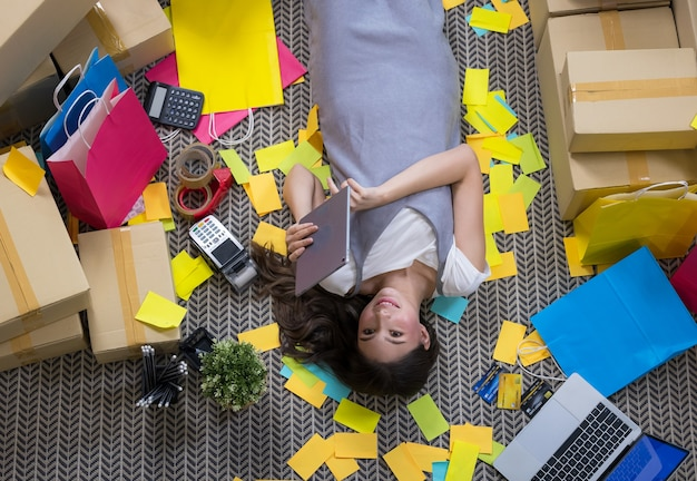 Top view portrait of creative young woman lying with eyes closed in art and design supplies scattered around, copy space
