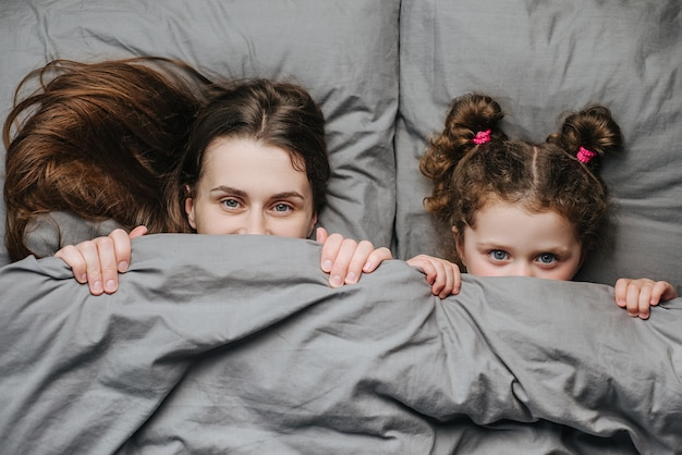 Top view portrait of cute funny kid daughter and young mother hides under soft blanket, has fun in bed, look at camera, rejoices good morning. smiling mom and little girl child have fun
