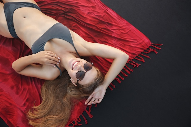 Top view portrait of happy, smiling woman in a swimsuit, lying on a beach towel on the beach.