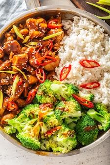 ご飯、唐辛子、蒸しブロッコリーを添えた和風鶏肉の上面図。
