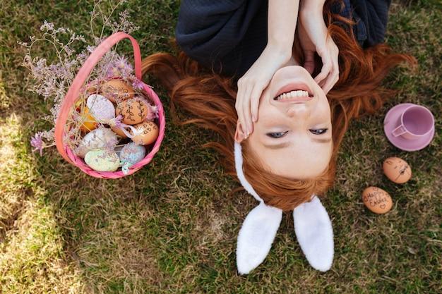 Портрет взгляд сверху усмехаясь счастливой красной головной женщины