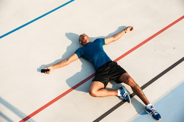 Портрет взгляд сверху утомленного молодого африканского человека фитнеса отдыхая