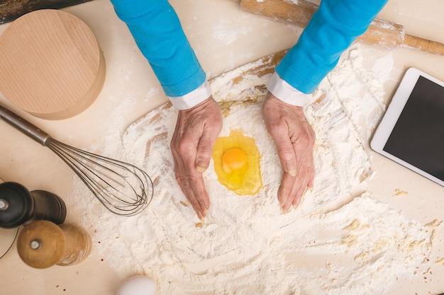 Портрет взгляд сверху привлекательной старшей постаретой женщины варит на кухне. бабушка делает вкусную выпечку.
