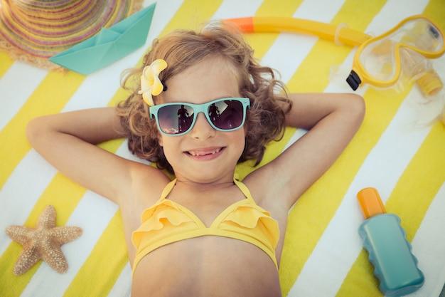 青いサングラスを着用し、縞模様のビーチタオルの上に横たわっている女の子の平面図の肖像画