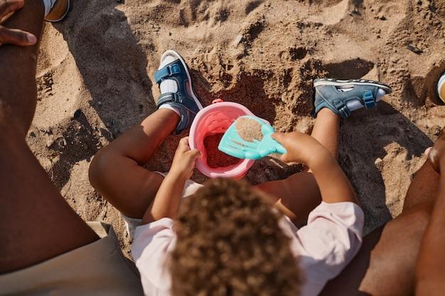 ビーチのコピースペースで一緒に砂で遊ぶ若いアフリカ系アメリカ人の父と息子の平面図の肖像画