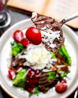 Вилка для съемки портретов сверху с жареным мясом и помидорами на гриле с овощами и салатом с тертым сыром на тарелке