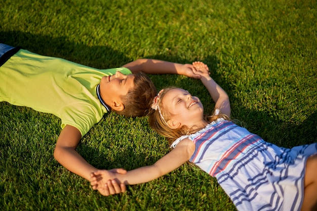 Top view portrait of two happy smiling kids lying on green grass.