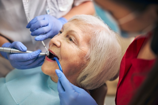 Top view portrait of woman patient sitting in medical chair while dentist professional filling teeth