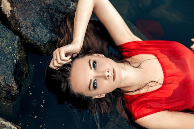 Top view portrait of young pretty wet woman mermaid lying on rock in the water river or lake touching head dressed in red dress looking at the camera copy space and nature blur background