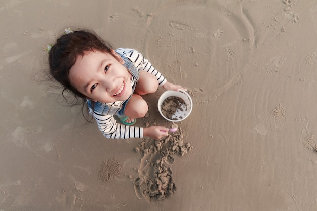 Top view portriat asian little girl playing on the sand beach with evening ambient