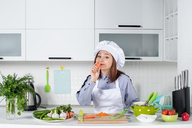 Vista dall'alto di chef positivo e verdure fresche con attrezzatura da cucina e degustazione di carote nella cucina bianca