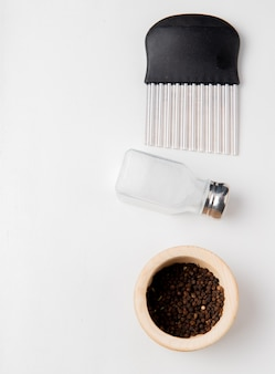Top view of potato chip cutter with salt and black pepper seeds on white surface with copy space