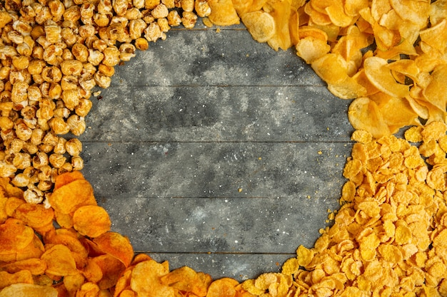 Top view of potato chips corn flakes and sweet popcorn with copy space