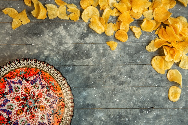 Top view of potato chips and a plate with oriental print with copy space