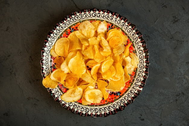 Top view of potato chips in a plate with oriental prints on black