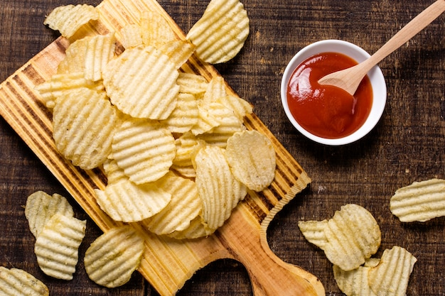Top view of potato chips with ketchup