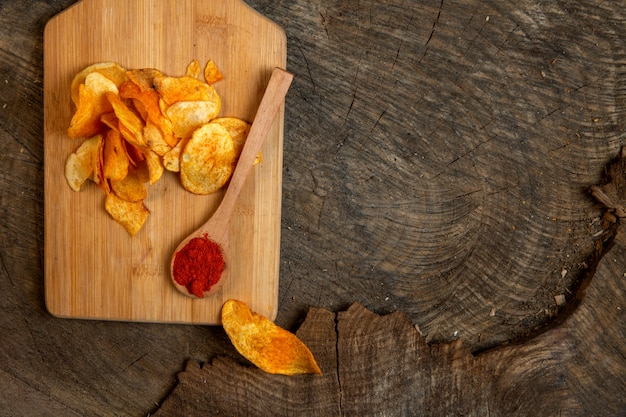 Top view of potato chips with a wooden spoon of chili pepper powder on a wooden cutting board with copy space