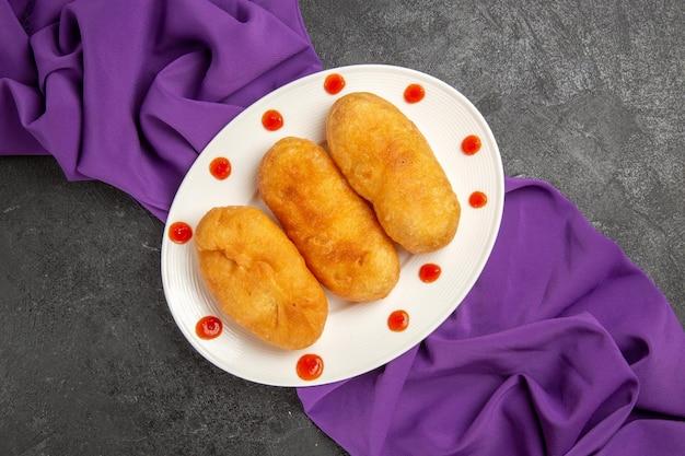 ダークグレーの背景に紫色のティッシュでプレート内のトップビューポテトホットケーキパイ焼きオーブンホットケーキケーキ