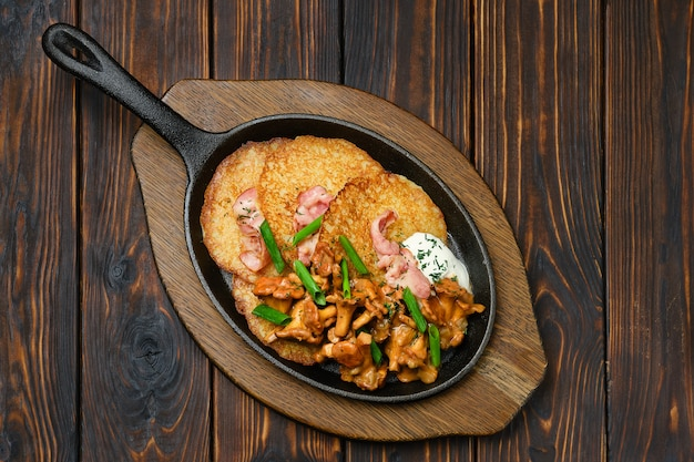 Top view of potato pancakes with chanterelles and pork in cast iron skillet