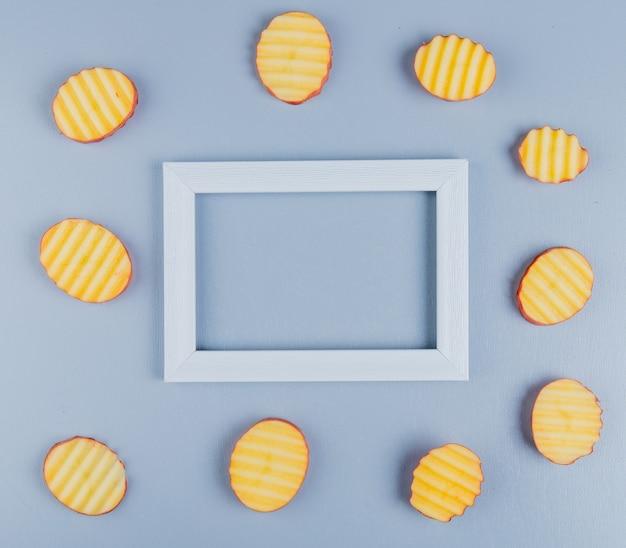 Vista dall'alto di fette di patate intorno al telaio sulla superficie blu con spazio di copia