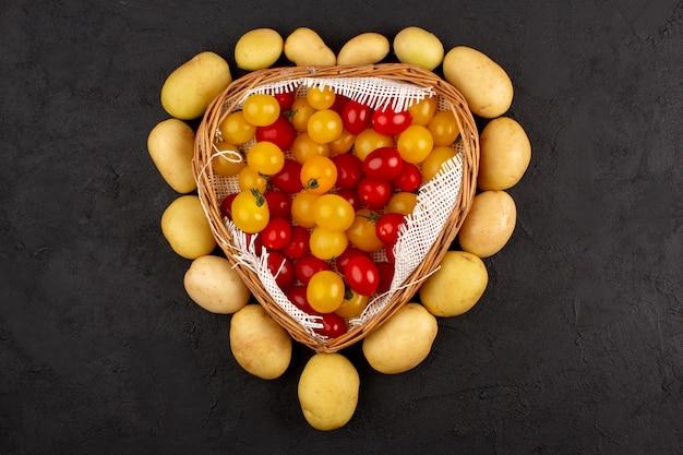 Vista dall'alto patate insieme a pomodori gialli e rossi su sfondo scuro