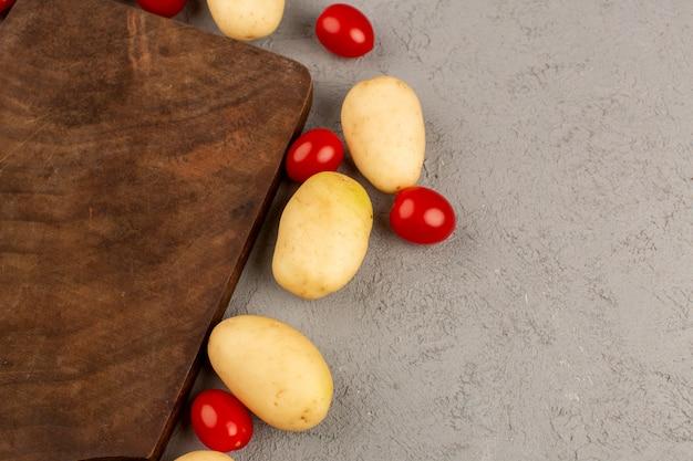 Вид сверху картофель и помидоры на сером