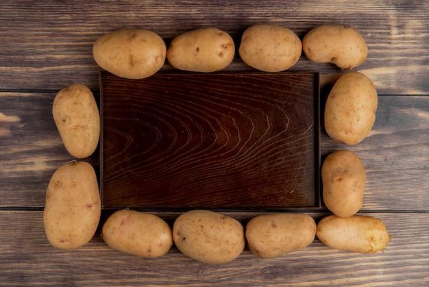 Vista superiore delle patate intorno al vassoio vuoto su legno