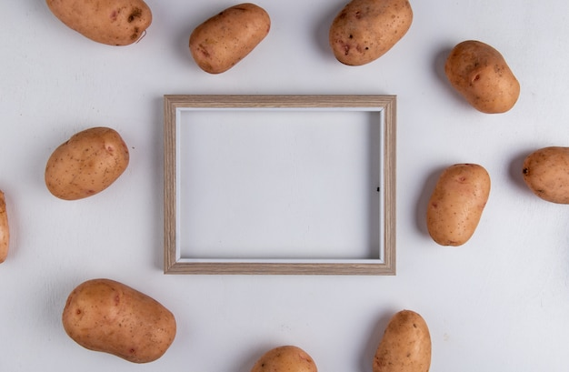 Top view of potatoes around frame on purple with copy space