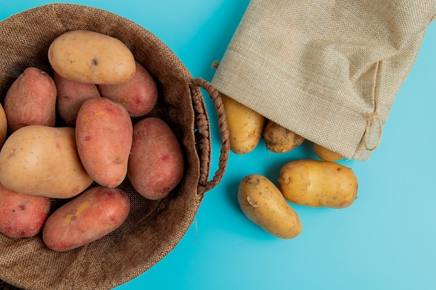 Top view of potatoes in basket and other ones spilling out of sack on blue surface
