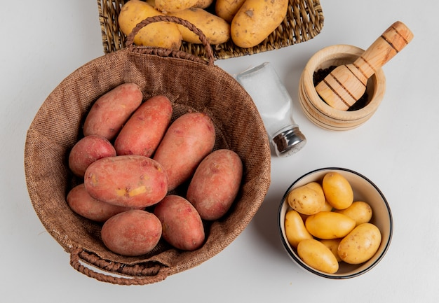 Top view of potatoes in basket and in plate with salt black pepper on white