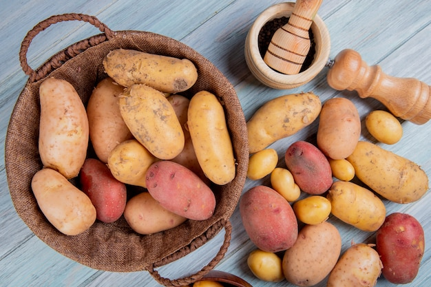 Vista superiore della merce nel carrello delle patate con il sale dei semi del pepe nero e altre patate su superficie di legno