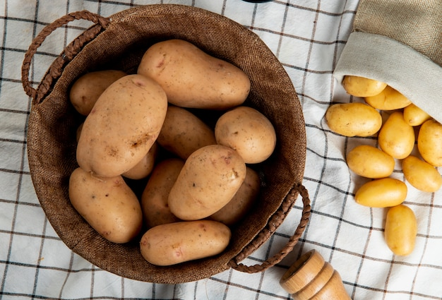 Top view of potatoes in basket with other ones spilling out of sack on plaid cloth surface