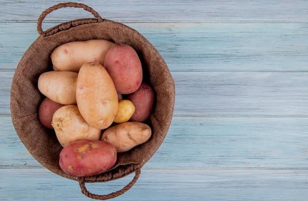 Vista superiore della merce nel carrello delle patate su superficie di legno con lo spazio della copia