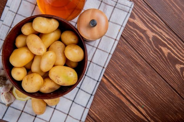 Vista superiore delle patate in ciotola con sale e burro di limone dell'aglio sul panno e sul legno del plaid con lo spazio della copia