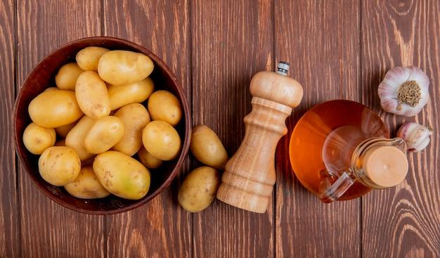 Vista superiore delle patate in ciotola con sale e burro di aglio su superficie di legno