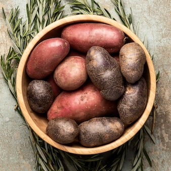 Top view of potatoes in bowl with rosemary