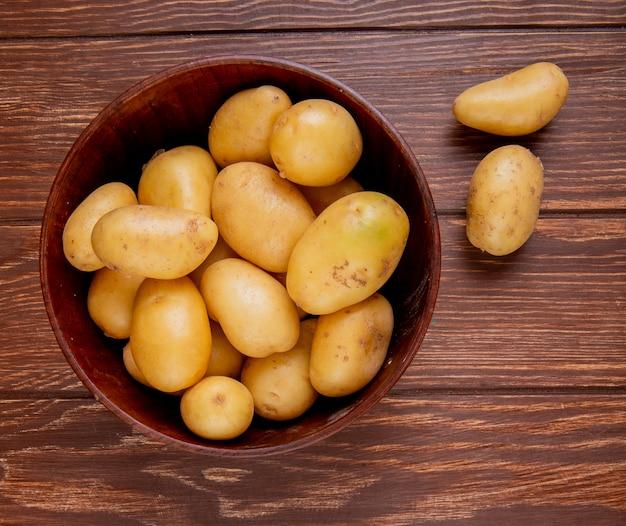 Vista superiore delle patate in ciotola su legno