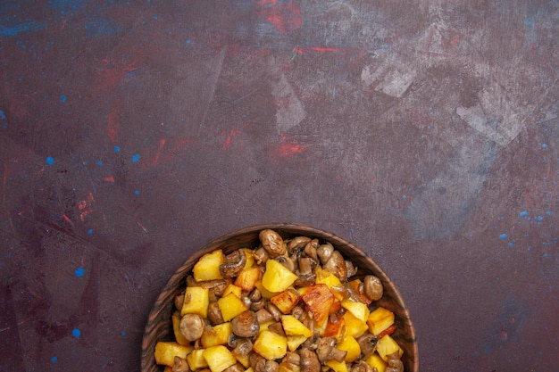 Vista dall'alto patate e funghi fritti sul fondo della superficie scura ci sono patate fritte con funghi in una ciotola marrone su una superficie viola
