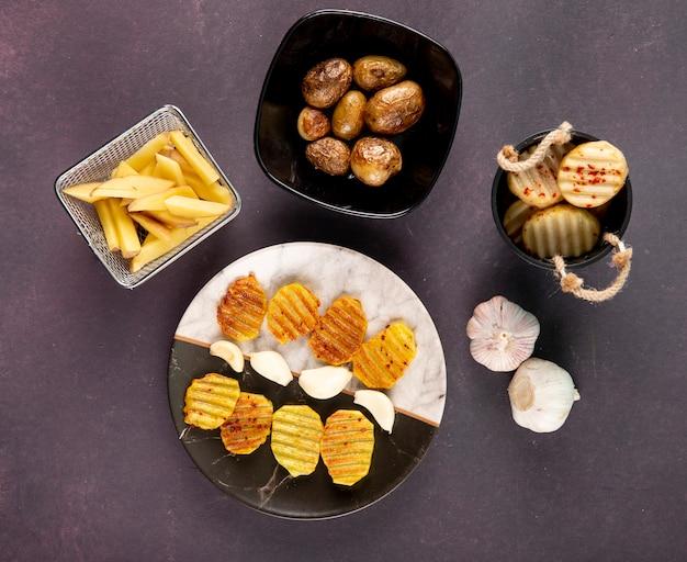 Вид сверху картофель гриль и нарезанный картофель с сушеными хлопьями чили и чесноком на темно-сером фоне