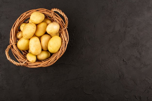 Вид сверху картофель в корзине на темном полу