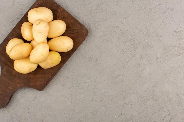 Vista dall'alto patate sbucciate sulla scrivania di legno marrone sul grigio