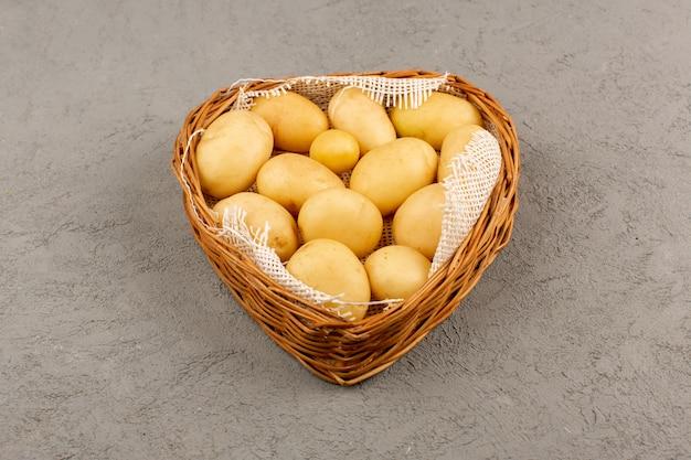 Vista dall'alto patate sbucciate fuori nel cestino sul grigio
