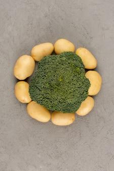 Вид сверху картофель очищенный от круглой формы с зеленой брокколи на сером полу