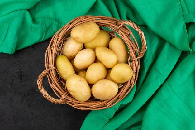 Vista dall'alto patate sbucciate nel cestino grigio sul pavimento grigio
