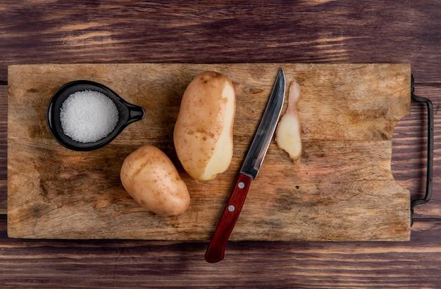 Vista superiore del coltello del sale delle patate sul tagliere su legno