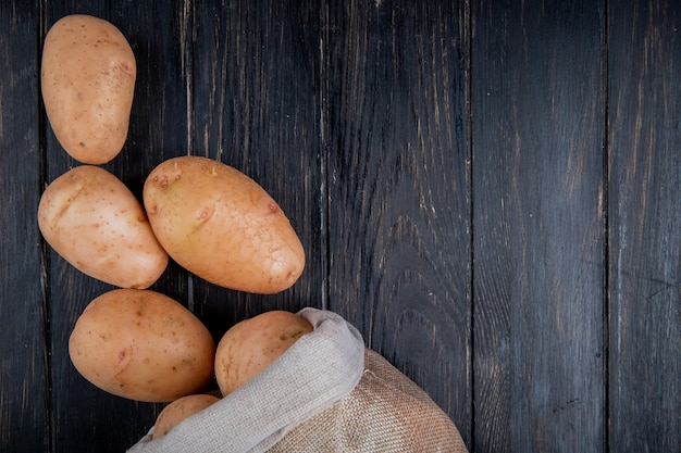 Top view of potatoes spilling out of sack on wooden surface with copy space